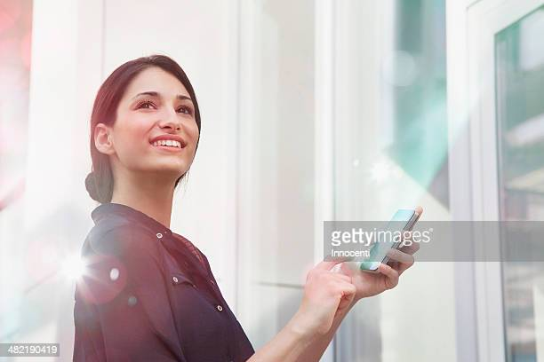 Young businesswoman holding smartphone with lights coming out of it