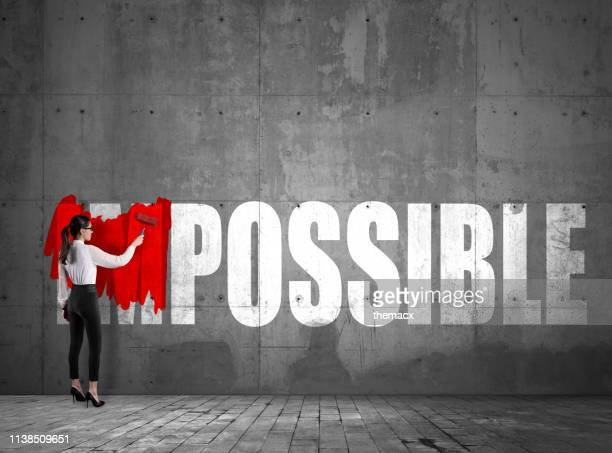 young businesswoman impossible text on the wall using red paint roller - possible stock pictures, royalty-free photos & images