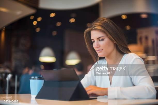 young businesswoman in a cafe using tablet - werkneemster stockfoto's en -beelden