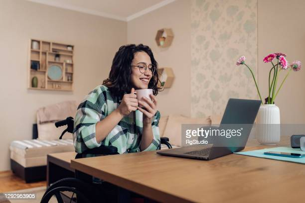 young businesswoman in a wheelchair enjoying coffee and working online from home - wheelchair stock pictures, royalty-free photos & images