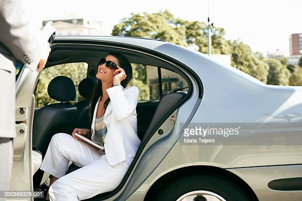 Young businesswoman in back seat of car smiling at man