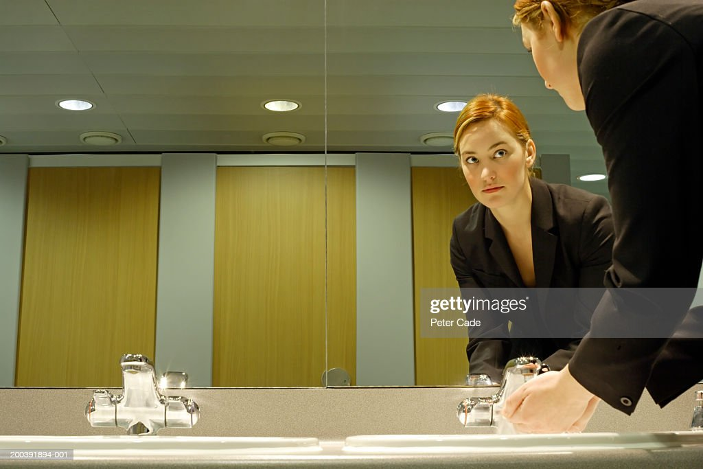 Young businesswoman in bathroom, washing hands : Stock Photo