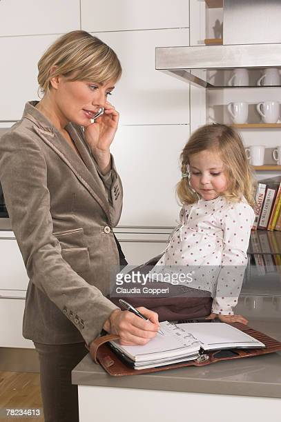 young businesswoman in kitchen looking at her daughter while listening to cellphone
