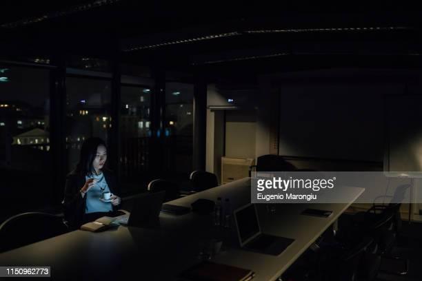young businesswoman in office at night looking at laptop - fare lo straordinario foto e immagini stock