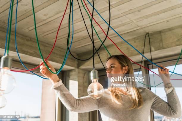 young businesswoman in office examining cables at light bulbs - con eficaz consumo de energía fotografías e imágenes de stock