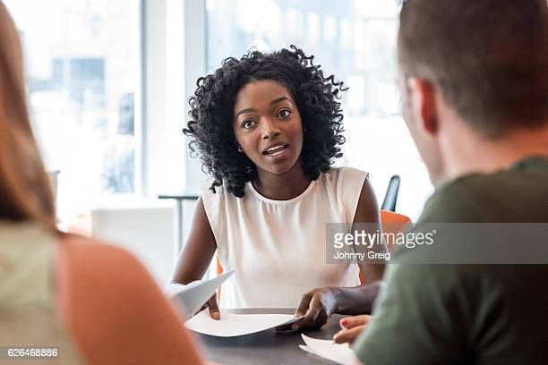 young businesswoman in office talking to colleagues, pensive expression - afro americano - fotografias e filmes do acervo