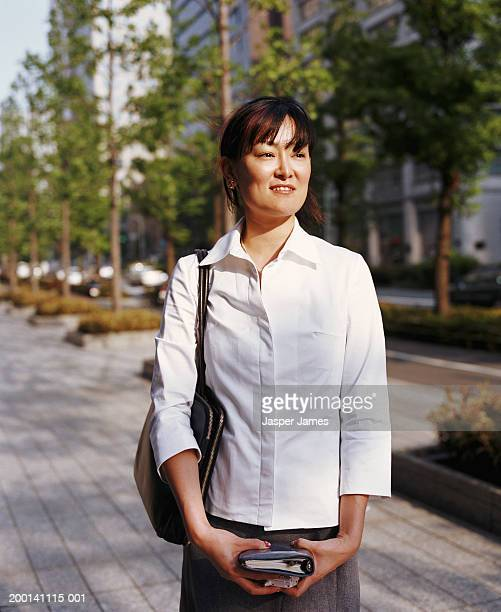 young businesswoman in street, holding phone and personal organiser - ショルダーバッグ ストックフォトと画像
