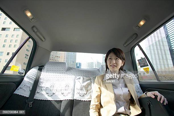 Young businesswoman in taxi, smiling, interior view