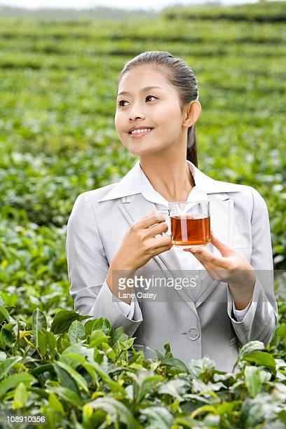 Young Businesswoman in Tea Field with Freshly Brewed Tea