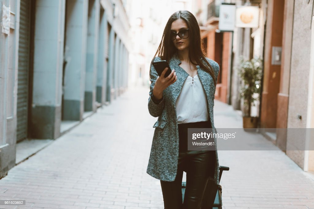 Young businesswoman in the city checking cell phone : Stock Photo
