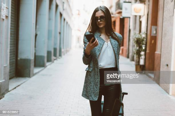 young businesswoman in the city checking cell phone - fashionable stock pictures, royalty-free photos & images
