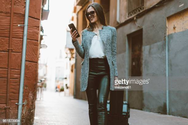 Young businesswoman in the city checking cell phone