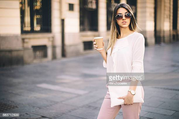 Young businesswoman in the city having a coffee break0