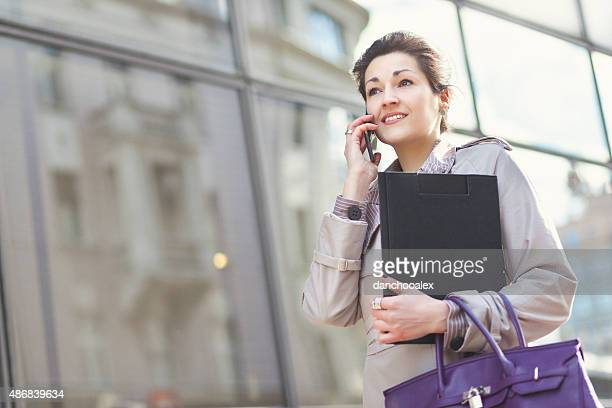 Young businesswoman in the city talking on the smart phone