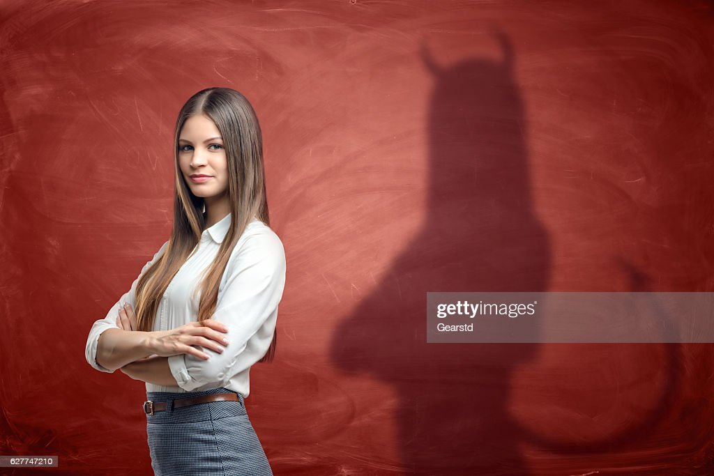 Young businesswoman is casting shadow of devil on rusty orange : Stock Photo