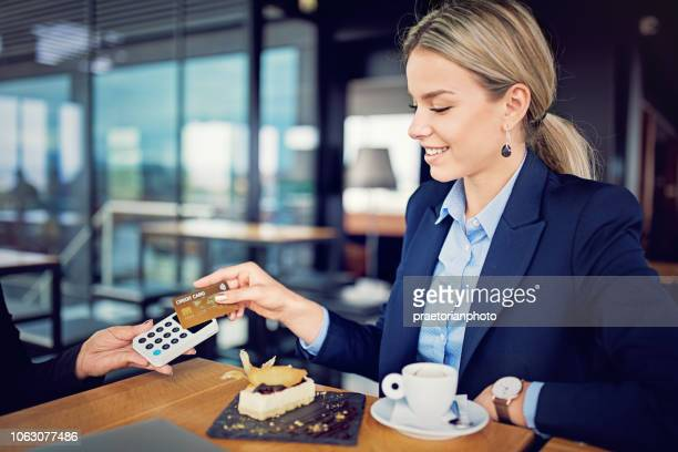 young businesswoman is paying using contactless credit card in a restaurant - nfc stock pictures, royalty-free photos & images