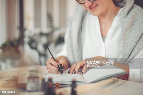 young businesswoman is writing in a personal organizer - calligraphy stock photos and pictures