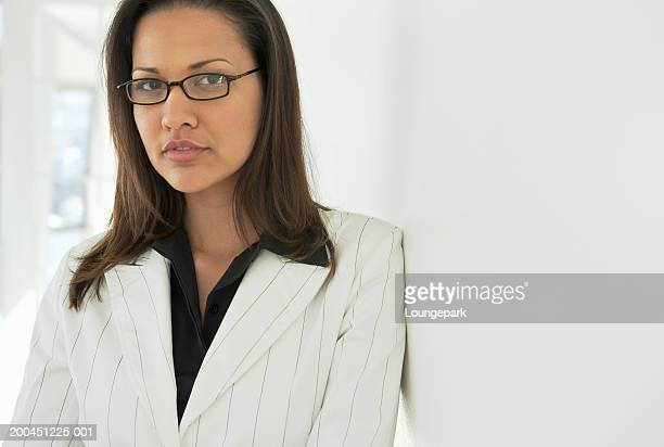 Young businesswoman leaning against wall, wearing spectacles, portrait