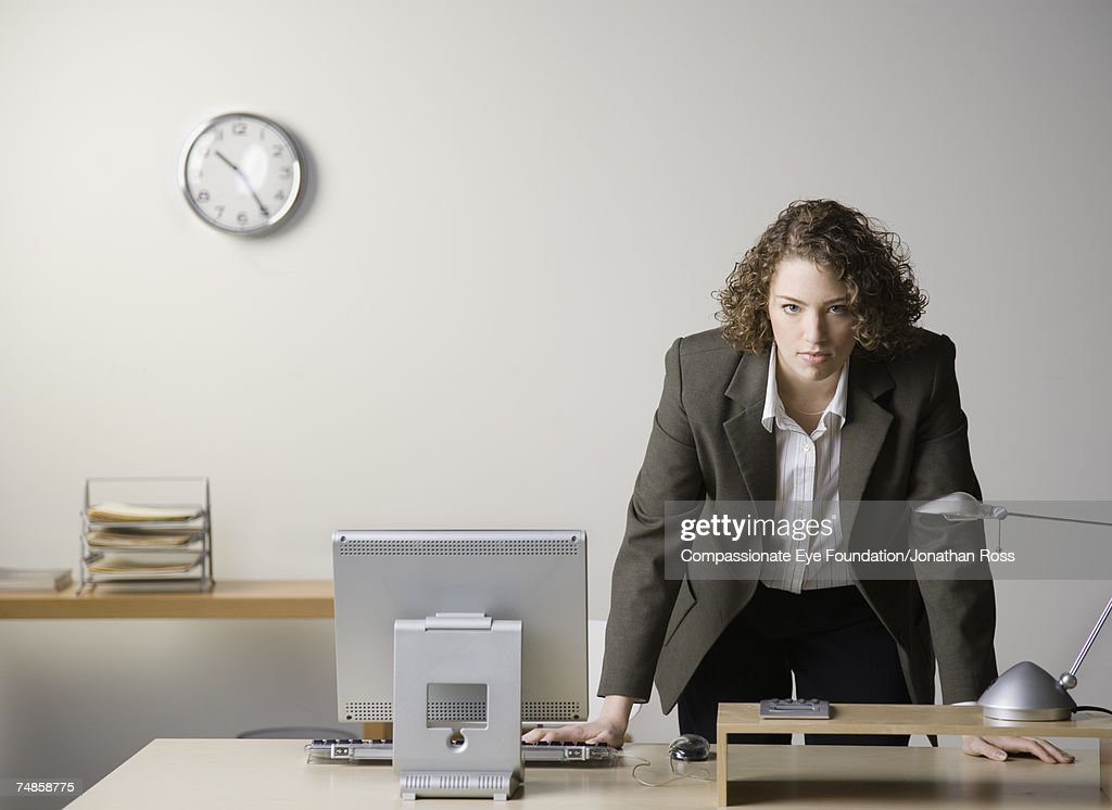 Young businesswoman leaning on desk in office, portrait : Stock Photo