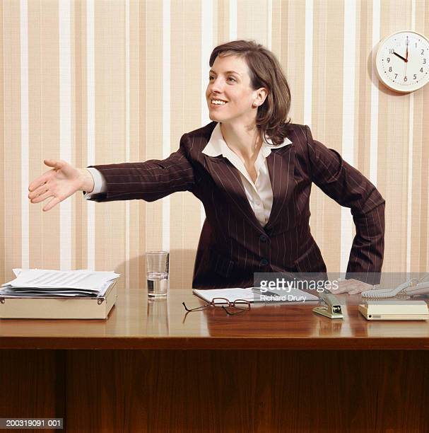 young businesswoman leaning over desk to shake hands, smiling - richard drury stock pictures, royalty-free photos & images