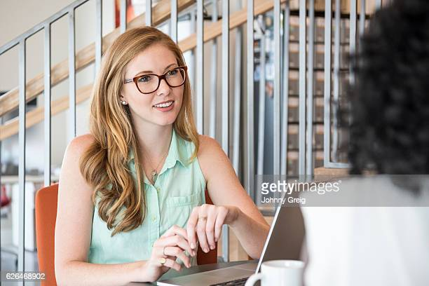 Young businesswoman listening to colleague, smiling