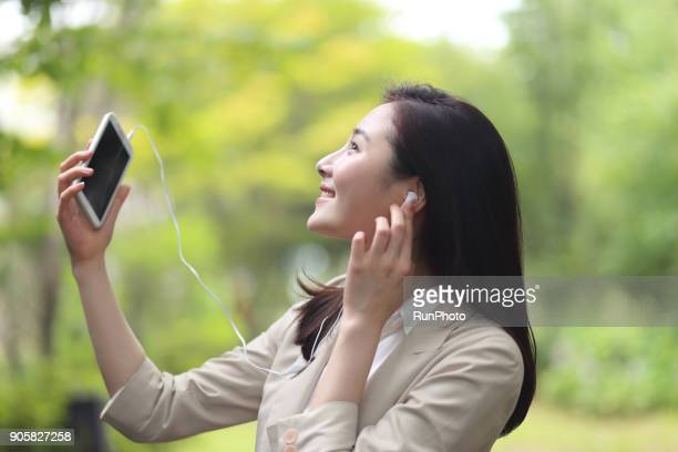 Young businesswoman listening to music with smartphone in park