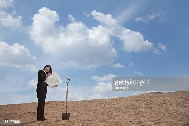 Young businesswoman looking at a blueprint next to a shovel in the middle of the desert