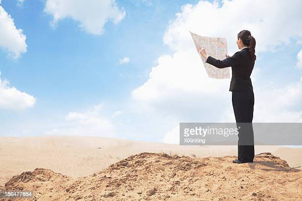 young businesswoman looking at a map in the middle of the desert - ポニーテール ストックフォトと画像