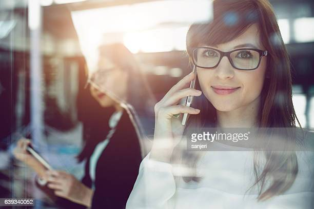 Young Businesswoman Looking at Camera Talking on Mobile Phone