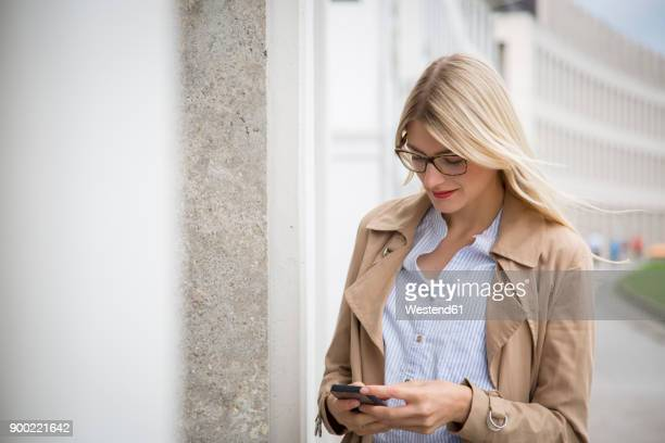 young businesswoman looking at cell phone - blonde glasses stock-fotos und bilder