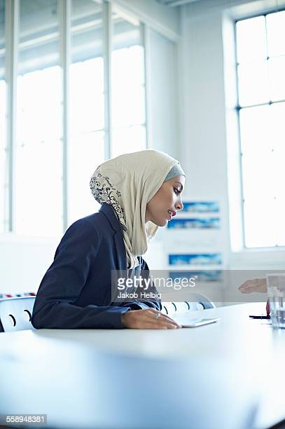 Young businesswoman looking at digital tablet in office meeting