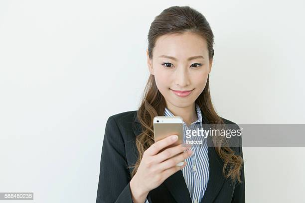 young businesswoman looking at mobile phone - 下を向く ストックフォトと画像