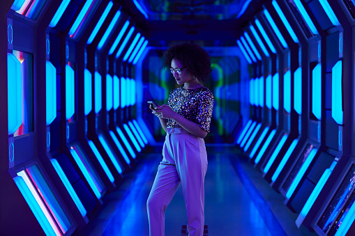 Young businesswoman looking at smartphone in spaceship like corridor - gettyimageskorea