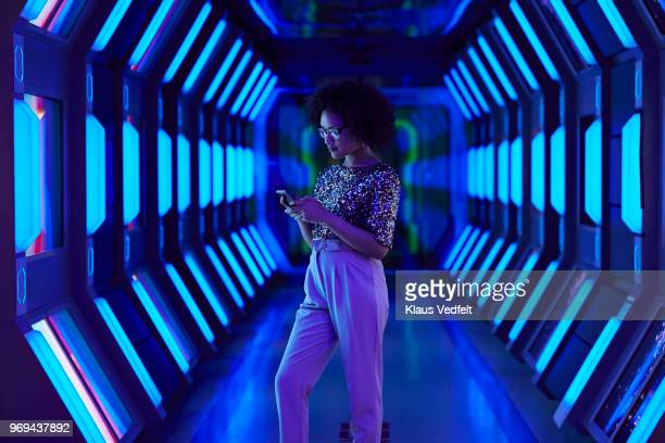 young businesswoman looking at smartphone in spaceship like corridor - tecnología fotografías e imágenes de stock