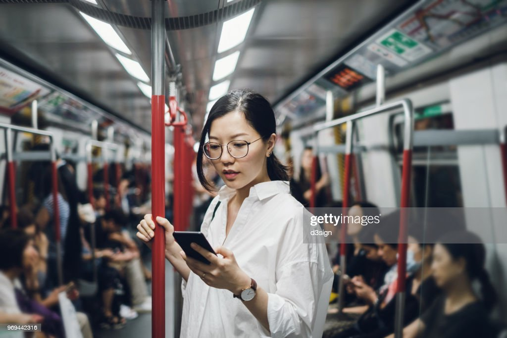 Young businesswoman looking at smartphone while riding on subway : Stockfoto