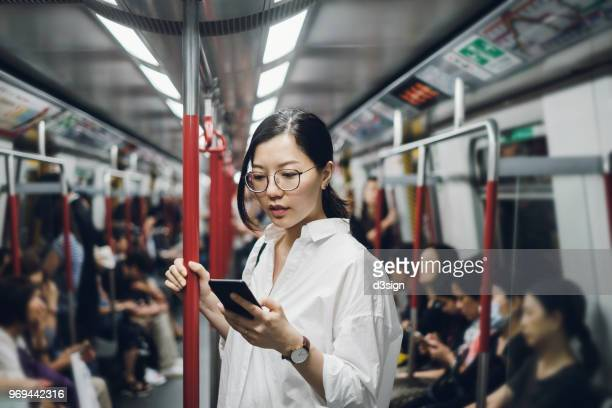 young businesswoman looking at smartphone while riding on subway - asien stock-fotos und bilder