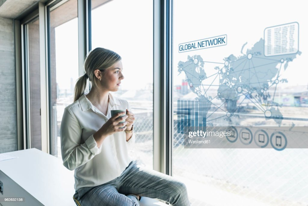 Young businesswoman looking at virtual world map at window pane in office : Stock Photo