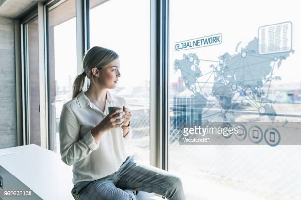 young businesswoman looking at virtual world map at window pane in office - internationale geschäftswelt stock-fotos und bilder