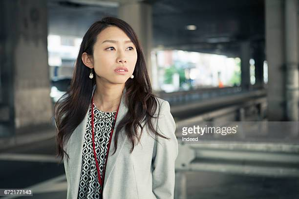 Young businesswoman looking away on street