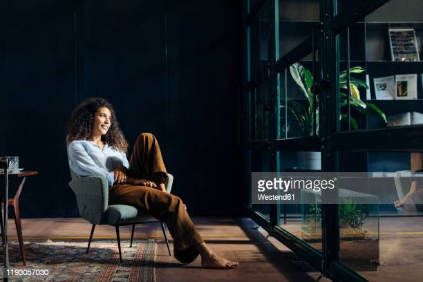 young businesswoman looking out of window in loft office - one young woman only stock pictures, royalty-free photos & images