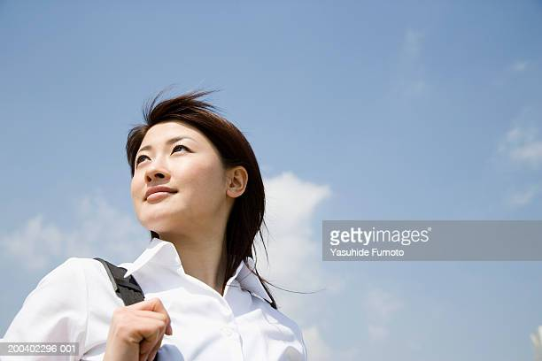 Young businesswoman looking over shoulder, outdoors, low angle view