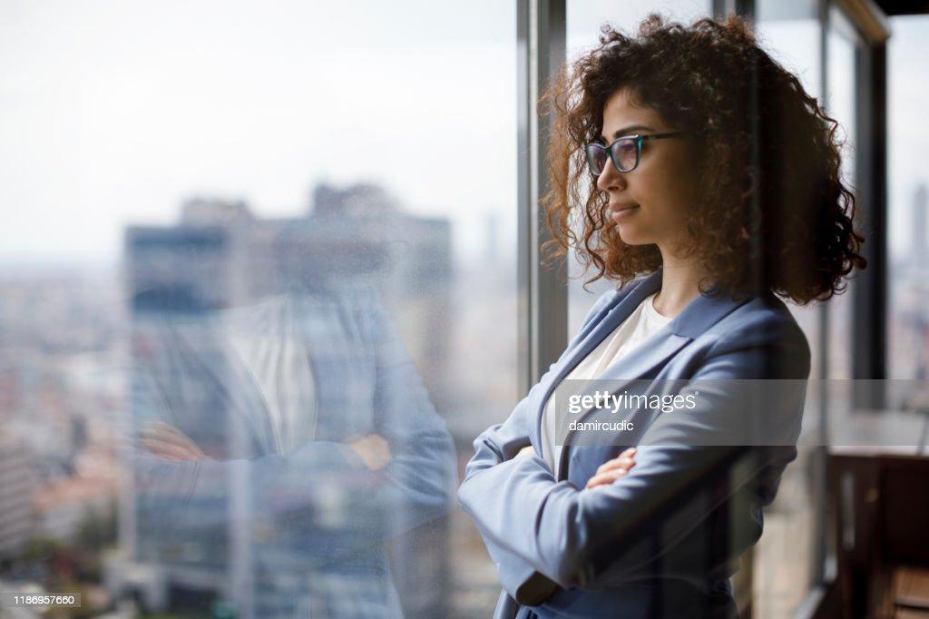 Jonge zakenvrouw kijken door venster : Stockfoto