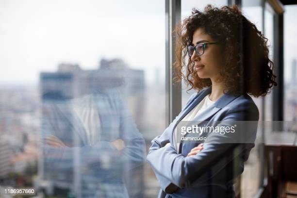 young businesswoman looking through window - contemplation stock pictures, royalty-free photos & images