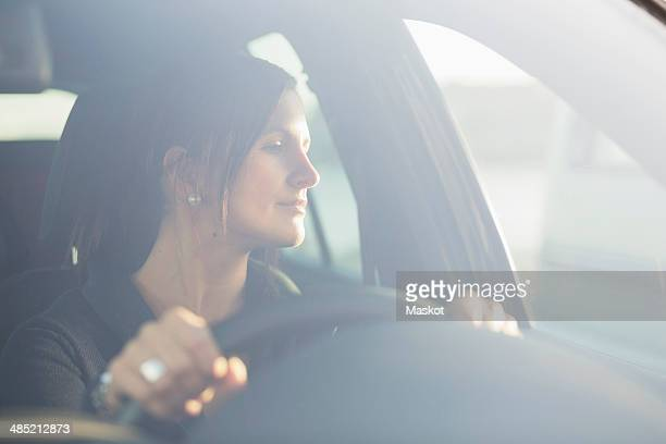Young businesswoman looking through window while driving car