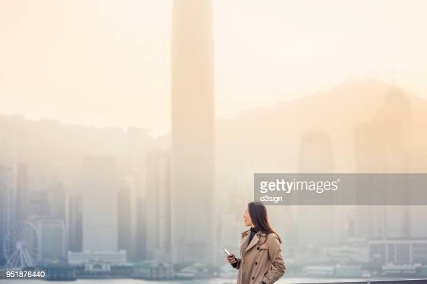 Young businesswoman looking towards city skyline with confidence