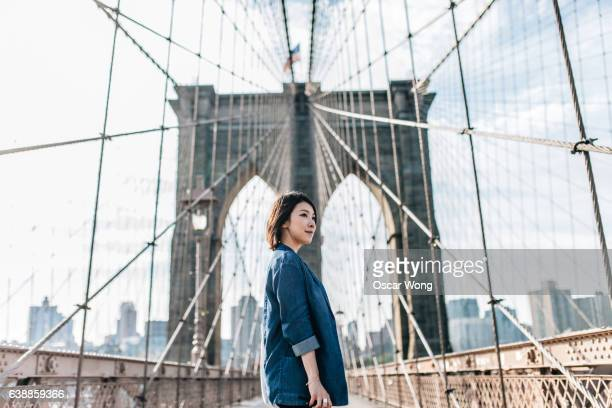 Young businesswoman looking up on Brooklyn Bridge against New York cityscape
