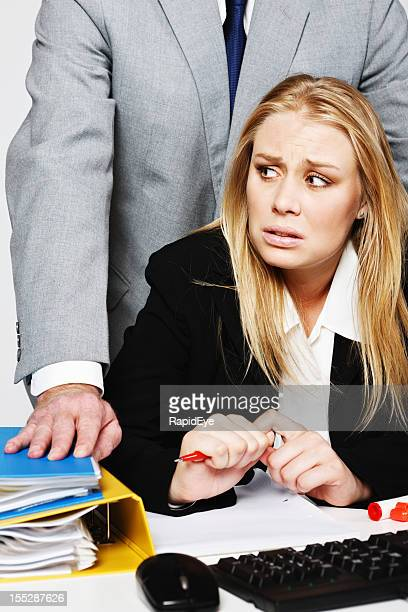 Young businesswoman looks round nervously at harassing man behind her