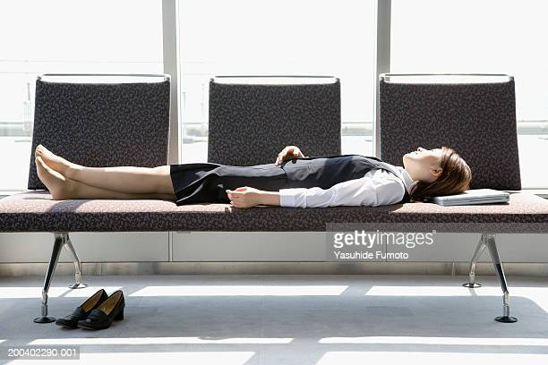 Young businesswoman lying on couch, resting head on laptop
