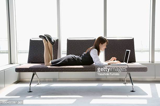 Young businesswoman lying on couch, working on laptop