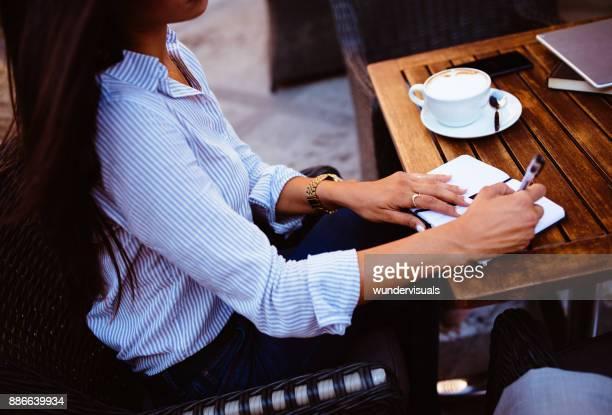 jovem empresária fazendo anotações no diário sentado no café urbano - diretor de cinema - fotografias e filmes do acervo